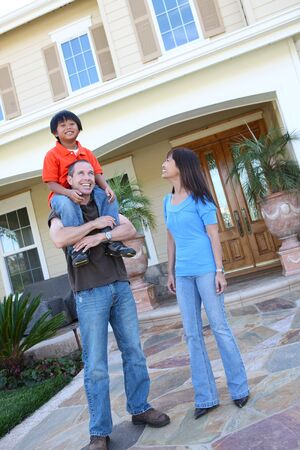 Attractive asian family outside their home having fun photo
