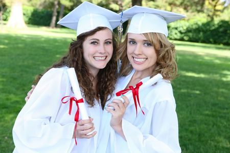Pretty young women at graduation hugging with diplomas Stock Photo - 5079651