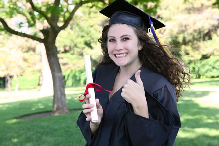 Pretty young woman at graduation giving thumbs up Stock Photo - 5079654