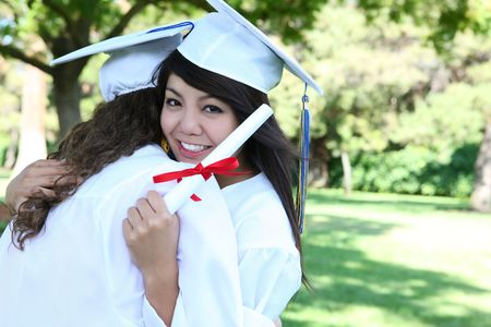 A pretty asian woman hugging a friend and holding her diploma at graduation photo