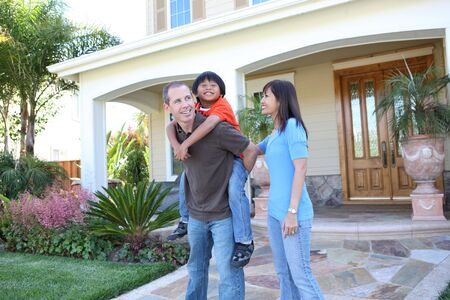 Attractive diverse family outside their home having fun photo