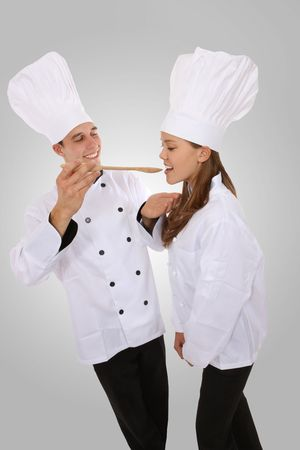 Attractive man and woman chef tasting food photo