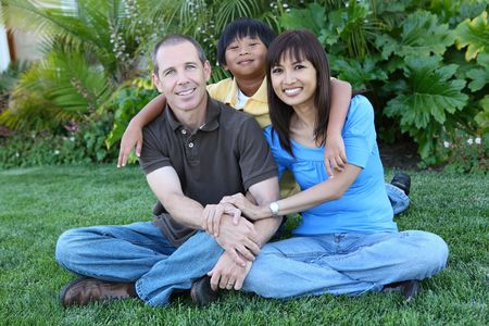 Attractive happy family outside their home having fun photo