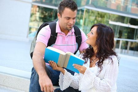 A man and woman student at school studying outside library photo