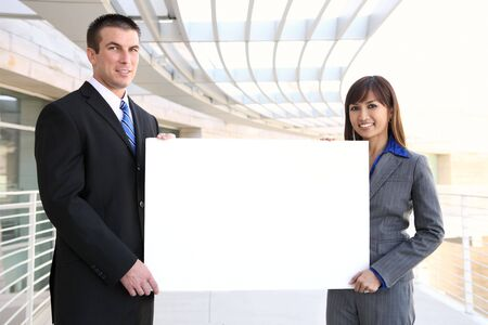 An attractive man and woman business team holding sign at office Stock Photo - 5145175