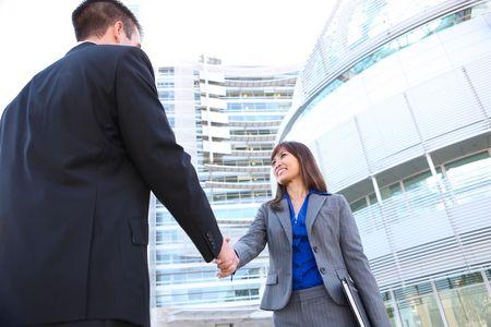 魅力的な男性と女性ビジネス チーム事務所ビルで握手