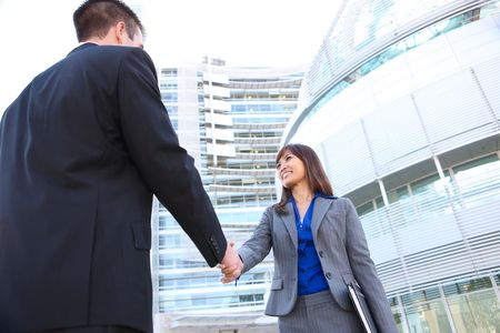An attractive man and woman business team shaking hands at office building Zdjęcie Seryjne