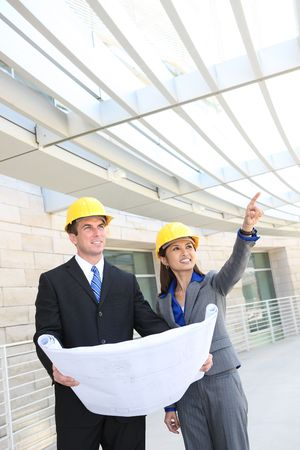 executive helmet: An attractive, diverse man and woman construction team at building site