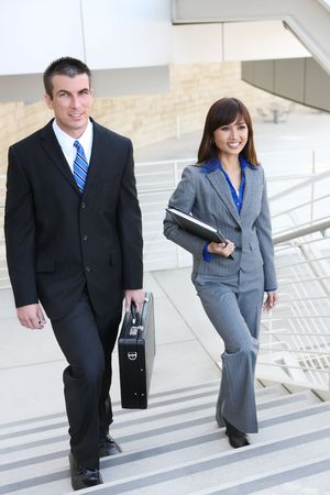 An attractive, diverse business man and woman team on stairs at office building photo