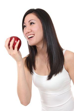 A happy pretty asian woman eating a fresh apple