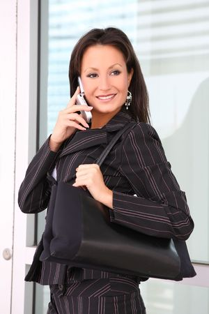 A young and pretty business woman on phone at office photo