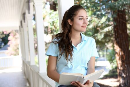 Pretty Girl Studying on Home Porch Reading Book photo