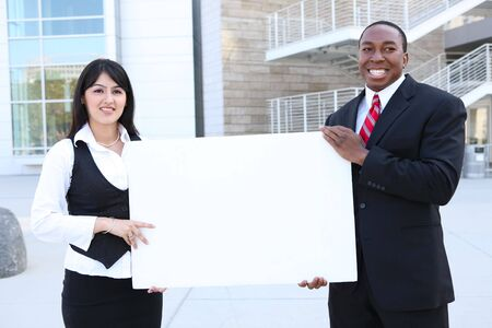 A young pretty indian business woman and african man holding a sign photo