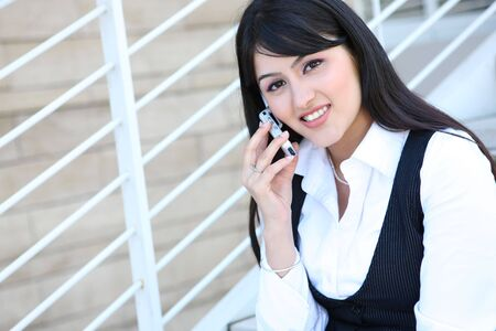 An Indian pretty business woman sitting on stairs using laptop photo