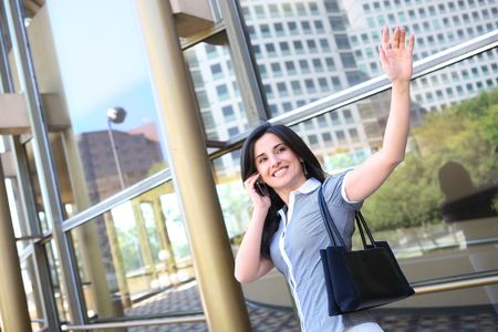 goodbye: A young pretty business woman waving goodbye at office building