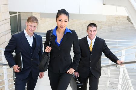 An attractive diverse business man and woman team walking up stairs photo
