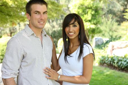 A sweet attractive man and woman couple in the park in love photo