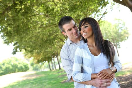 interracial relationships: An attractive man and woman couple in the park in love
