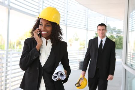 A young woman working as architect on a construction site with coworker in background   photo