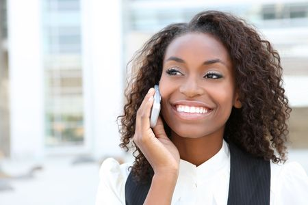 phone business: African american business woman talking on a  cell phone in front of an office building  Stock Photo