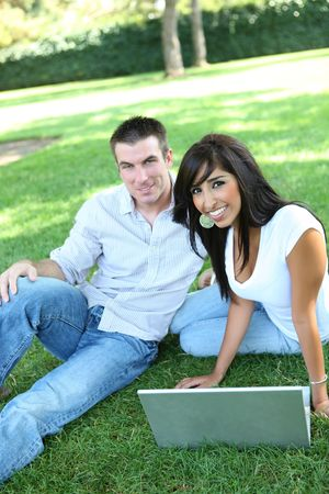 An attractive man and woman couple in the park with a laptop computer photo
