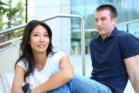 interracial couple: An Attractive man and woman Interracial couple in love at school Stock Photo
