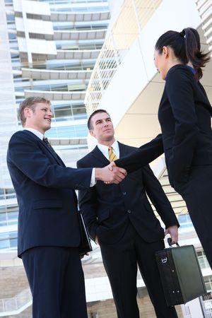 握手のオフィスでのビジネスの男性と女性チーム