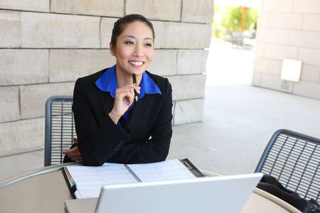 A young pretty asian business woman on laptop computer photo
