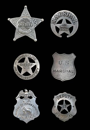 Several old, vintage sheriff, marshall, and police badges isolated over black photo