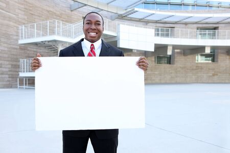 An attractive african american business man holding a sign at work office Stock Photo