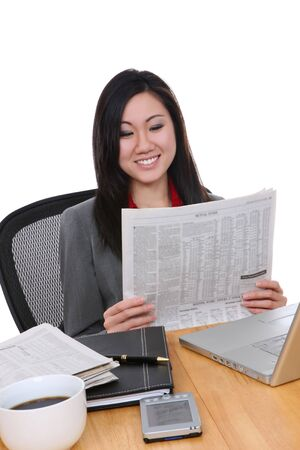 An attractive asian business woman in office on reading newspaper photo