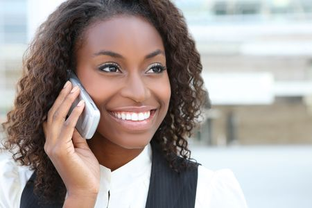 A pretty African american business woman talking on a  cell phone at office building  photo