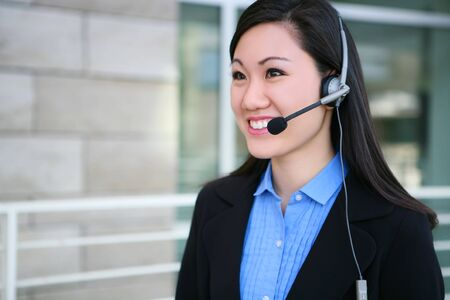 phone business: A young, pretty asian business woman at office building Stock Photo