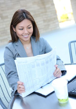 A pretty asian business woman at office reading newspaper photo