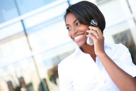 sexy business woman: A pretty African american business woman talking on a cell phone at office building  Stock Photo