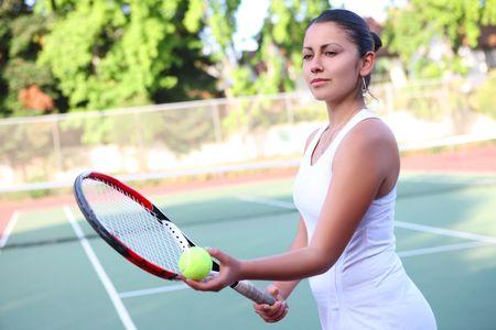 꽤 젊은 여자 테니스 선수가 공을 제공 준비