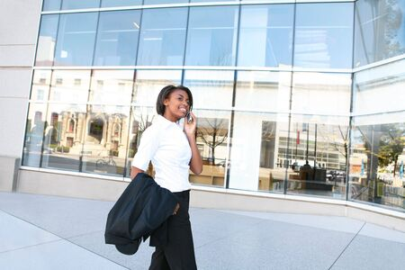 A pretty african american student woman on the cell phone in front of library Stock Photo - 5768766