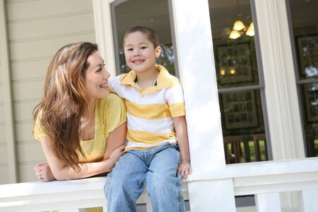 A cute boy and his mother on the porch at home photo