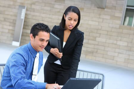 sales person: A diverse man and woman business team at their company office building on laptop computer Stock Photo