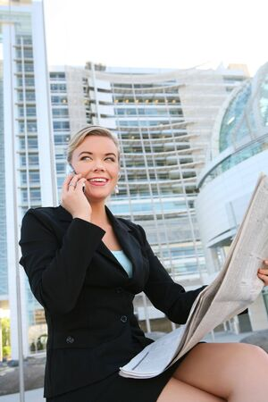 A beautiful blonde business woman in front of office building reading newspaper photo