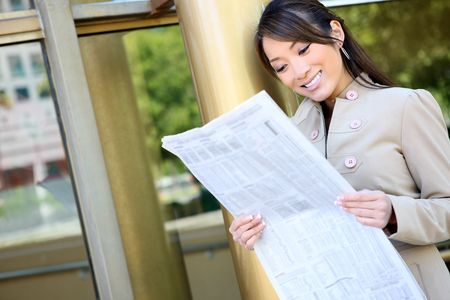 A pretty asian business woman reading the newspaper at office building photo