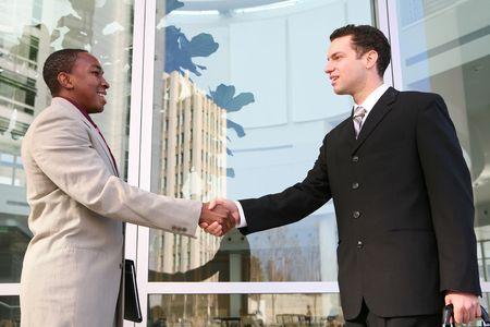 communication occupation: Un polo di attrazione, la squadra di uomo d'affari diverse si stringono la mano alla costruzione di ufficio