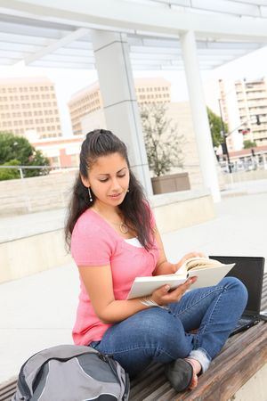 A pretty young teenage girl reading a book outside school building