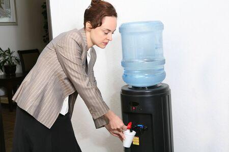 A pretty woman taking a water break in the office photo