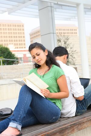 Attractive man and woman students at college studying reading a book photo