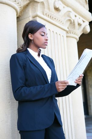 A young and pretty african american woman at college reading newspaper Stock Photo - 5939531