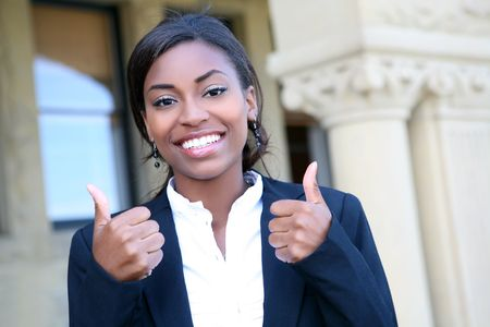 A pretty african american woman student at college with thumbs up Stock Photo - 5948409