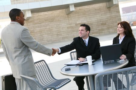 An attractive, diverse business man and woman team shaking hands at office building photo