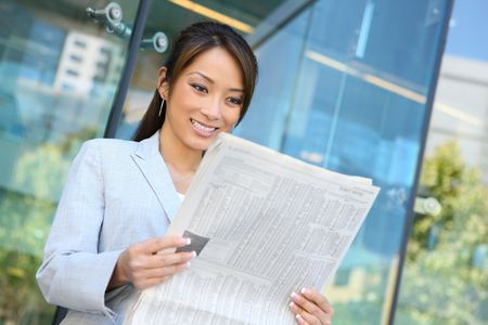 smart investing: A young attractive asian business woman reading  newspaper  Stock Photo