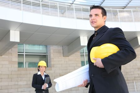 A handsome business man architect on contruction site with woman co-worker photo